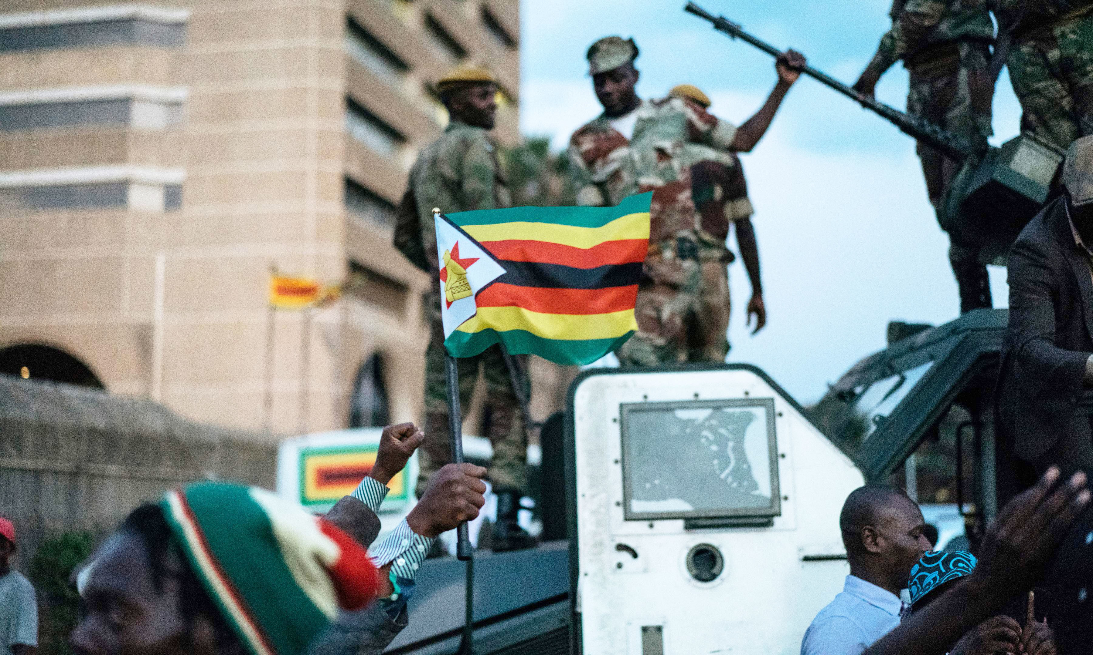 A man holds up the national flag of Zimbabwe as Zimbabwean soldiers are celebrated by citizens in the streets in Harare, on November 21, 2017 after the resignation of Zimbabwe's president Robert Mugabe. AFP PHOTO / MARCO LONGARI